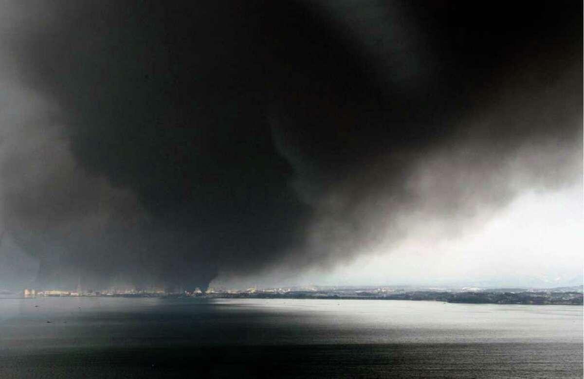 Black thick smokes cover the sky over Tagajo, Miyagi, northern Japan Saturday, March 12, 2011 after Japan's biggest recorded earthquake slammed into its eastern coast Friday. (AP Photo/Kyodo News) MANDATORY CREDIT, NO LICENSING ALLOWED IN CHINA, HONG KONG, JAPAN, SOUTH KOREA AND FRANCE