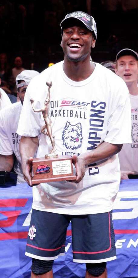 Connecticut's Kemba Walker (15) holds the Most Outstanding player trophy after an NCAA college basketball game against Louisville at the Big East Championship Saturday, March 12, 2011, in New York.  Connecticut won the game 69-66. (AP Photo/Frank Franklin II) Photo: AP