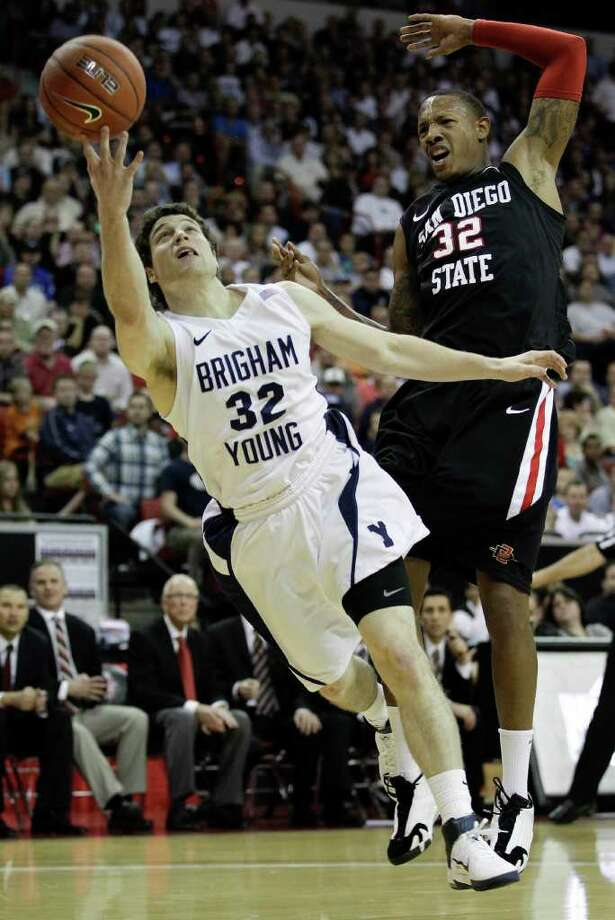 BYU's Jimmer Fredette, left, puts up a shot against San Diego State's Billy White during the first half of an NCAA college basketball game in the championship game of the Mountain West Conference tournament, Saturday, March 12, 2011, in Las Vegas. (AP Photo/Julie Jacobson) Photo: Julie Jacobson