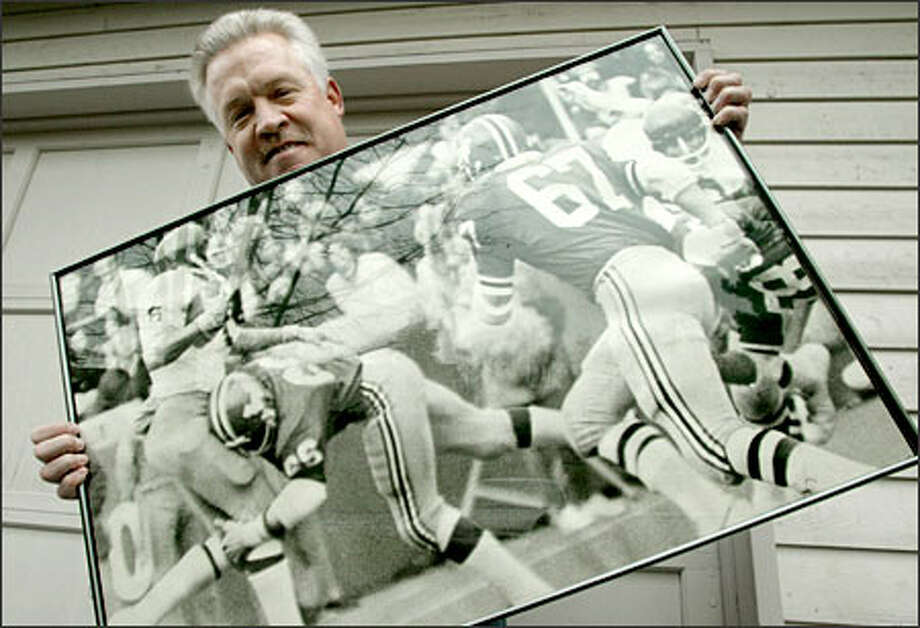 Former WSU linebacker Gary Larsen holds a photo of him putting a hit on UW quarterback Sonny Sixkiller during the 1972 Apple Cup. Photo: Gilbert W. Arias/Seattle Post-Intelligencer