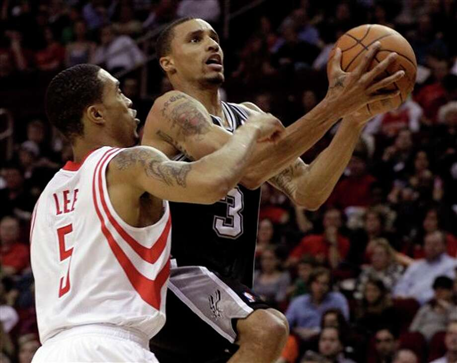 The Spurs' George Hill shashes to the basket on the Rockets' Courtney  Lee during the first half Saturday night. Hill finished with 14 points  off the bench. (PAT SULLVIAN/ASSOCIATED PRESS)