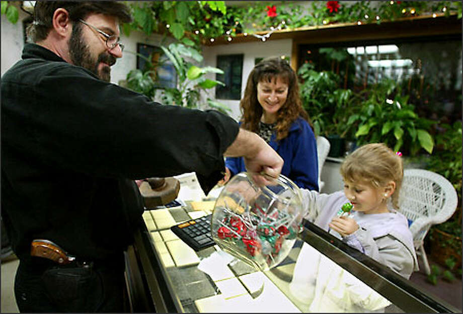 Chuck Hohner offers Laura Gillespie, 8, a second lollipop at his Kent store, Jewelry By Hohner. Hohner believes it is necessary to wear a gun on his hip after an armed robbery two months ago during which he was assured he would be killed. With Laura is her mom, Bonney Mock. Photo: Meryl Schenker/Seattle Post-Intelligencer