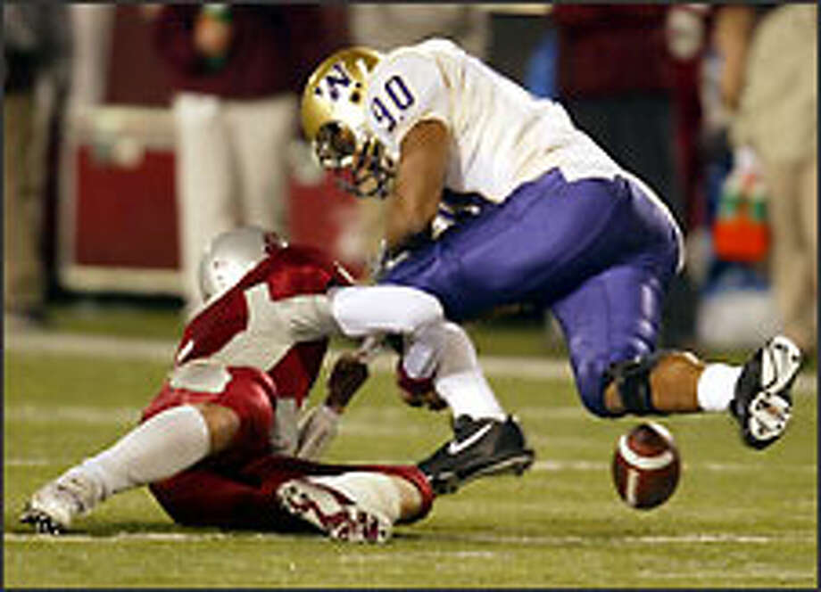 Kai Ellis forces a fumble -- it was ruled a backward pass -- by Cougars backup quarterback Matt Kegel that the UW defensive end recovered in the third overtime. Photo: Grant M. Haller/Seattle Post-Intelligencer