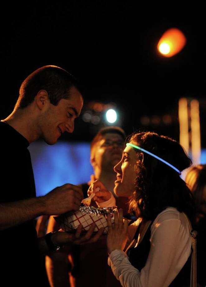 Mike Chapman and Sharon Friedman share nachos as flaming lanterns fly over them during the closing ceremony of Luminaria in HemisFair Park on Saturday, March 12, 2011. Photo: BILLY CALZADA, Billy Calzada/Express-News / gcalzada@express-news.net