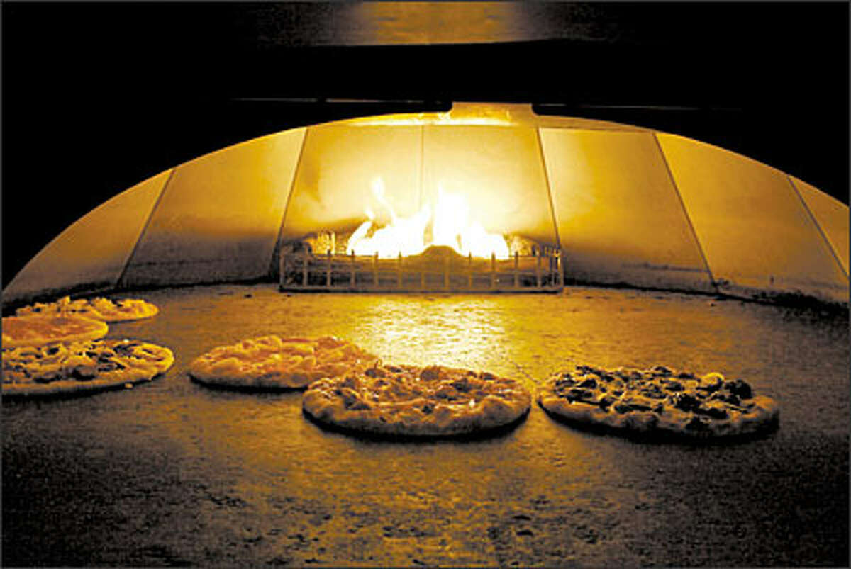 Pizzas bake in the oven at a California Pizza Kitchen.