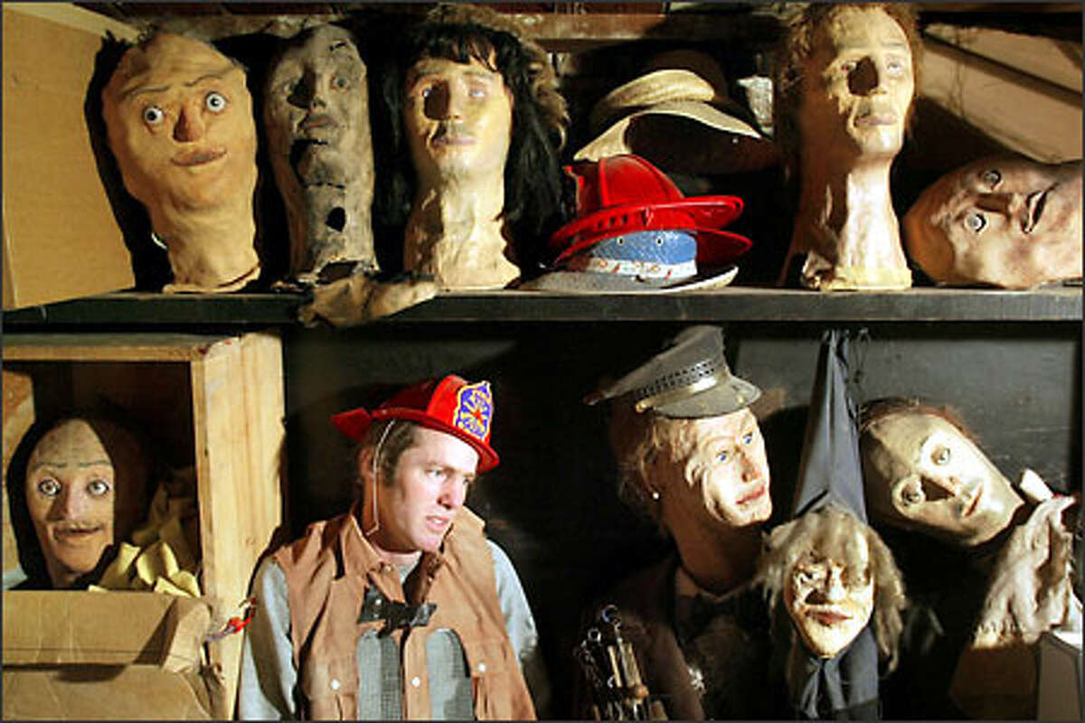 Nathan Arnold poses among some of his puppets in the basement of his University District home. His work often combines gee-whiz science experiments with art.