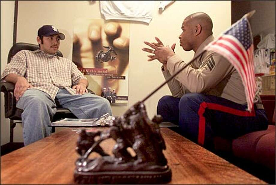 With a replica of the Iwo Jima Monument in the foreground, Sgt. James Turner, a Marine Corps recruiter, talks to Marco Valdez about signing up, in Turner's north Seattle office. Photo: Scott Eklund/Seattle Post-Intelligencer