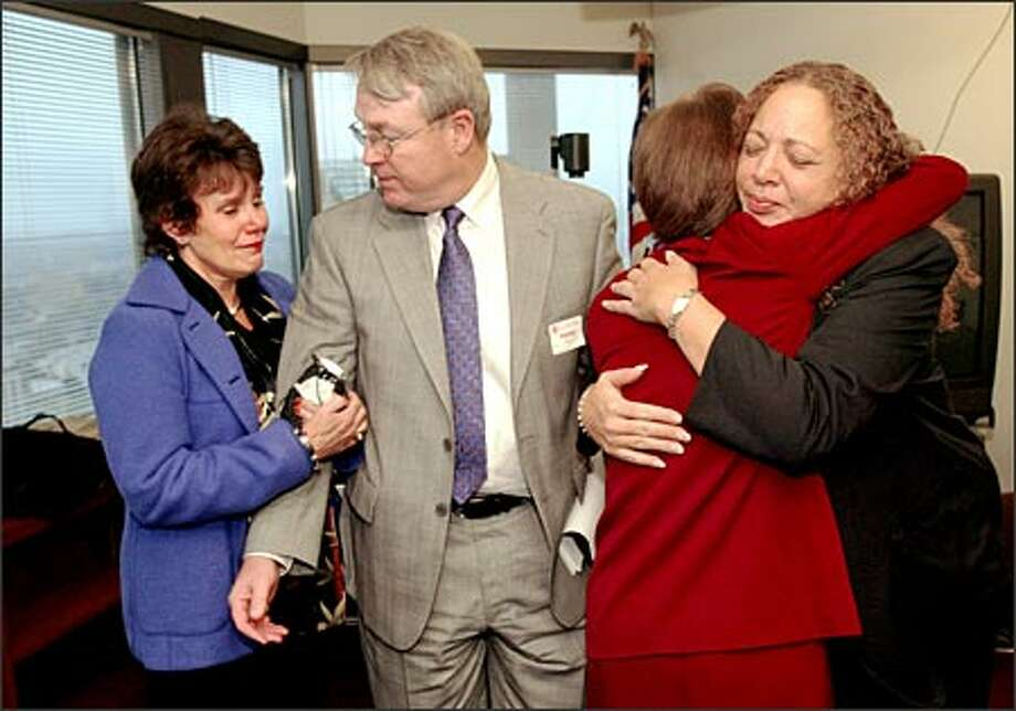 Assistant U.S. Attorney Helen Brunner (back to camera) hugs Katherine Dalen, mother of Stephen Tsiorvas, one of two boys killed in the 1999 pipeline explosion, as they and Frank and Mary King, parents of the other boy, Wade King, leave a news conference following announcement of guilty pleas. Photo: Phil H. Webber/Seattle Post-Intelligencer