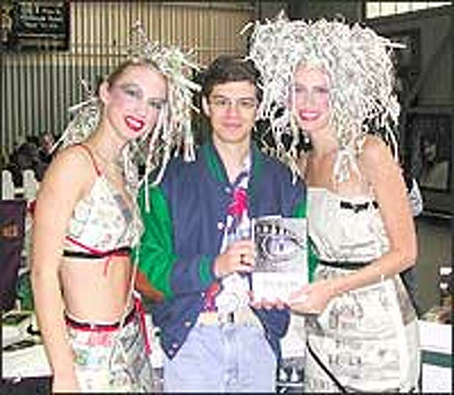 Christopher Paolini, shown with models Patricia O'Ryan, left, and Sabrina Carter promoting a hair salon during Northwest Bookfest, has signed a publishing deal reportedly worth more than $500,000. Photo: KENNETH PAOLINI