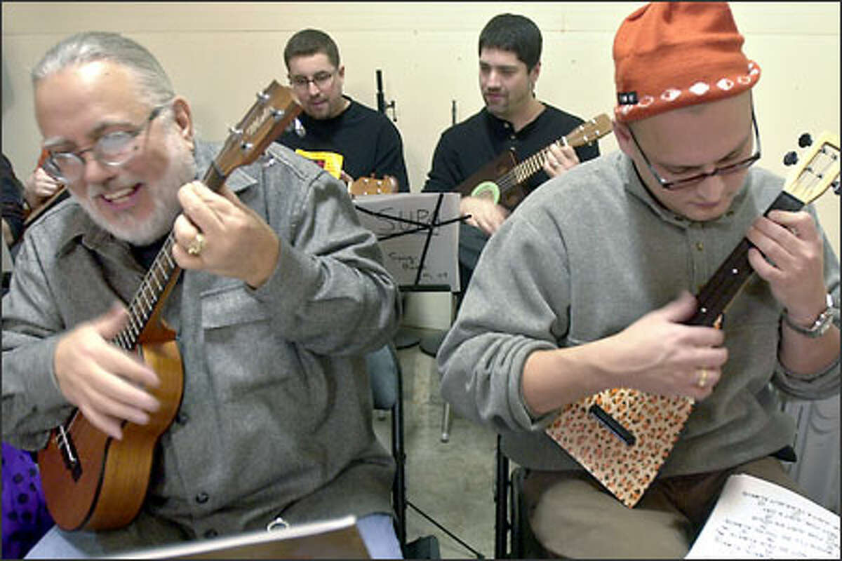 Pat Klopich, far left, and Stephen Arulaid, far right, play their ukuleles at the first gathering of the Seattle Ukulele Players Association held in Fremont yesterday. Nearly 40 musicians and wannabes showed up at Dusty Strings Acoustic Music Shop.