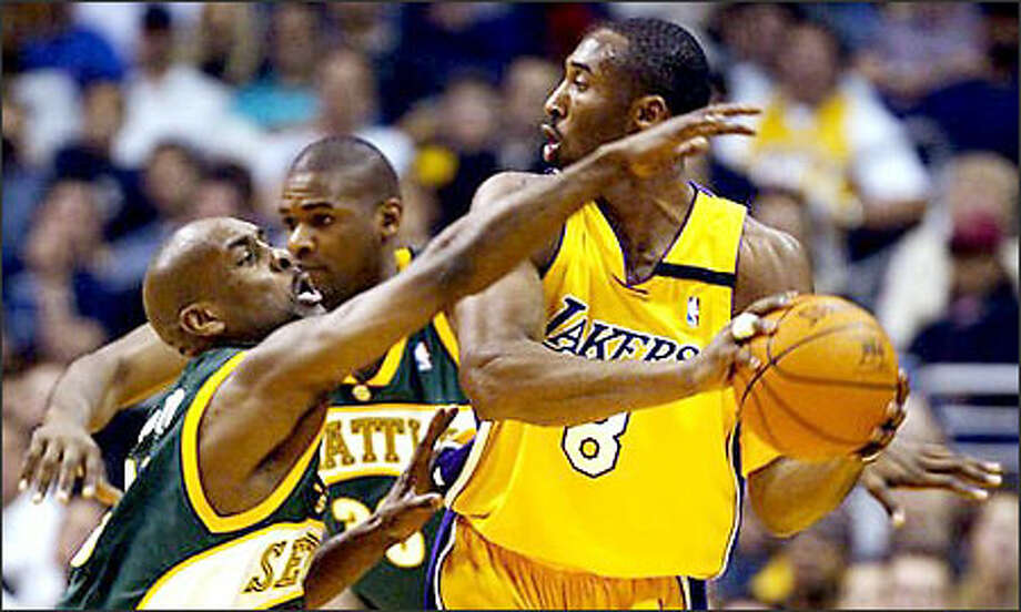 Kobe Bryant looks to pass against the aggressive defense of Gary Payton. In addition to his 12 3-pointers, Bryant set a record by hitting nine in a row. He scored 45 points. Photo: / Associated Press