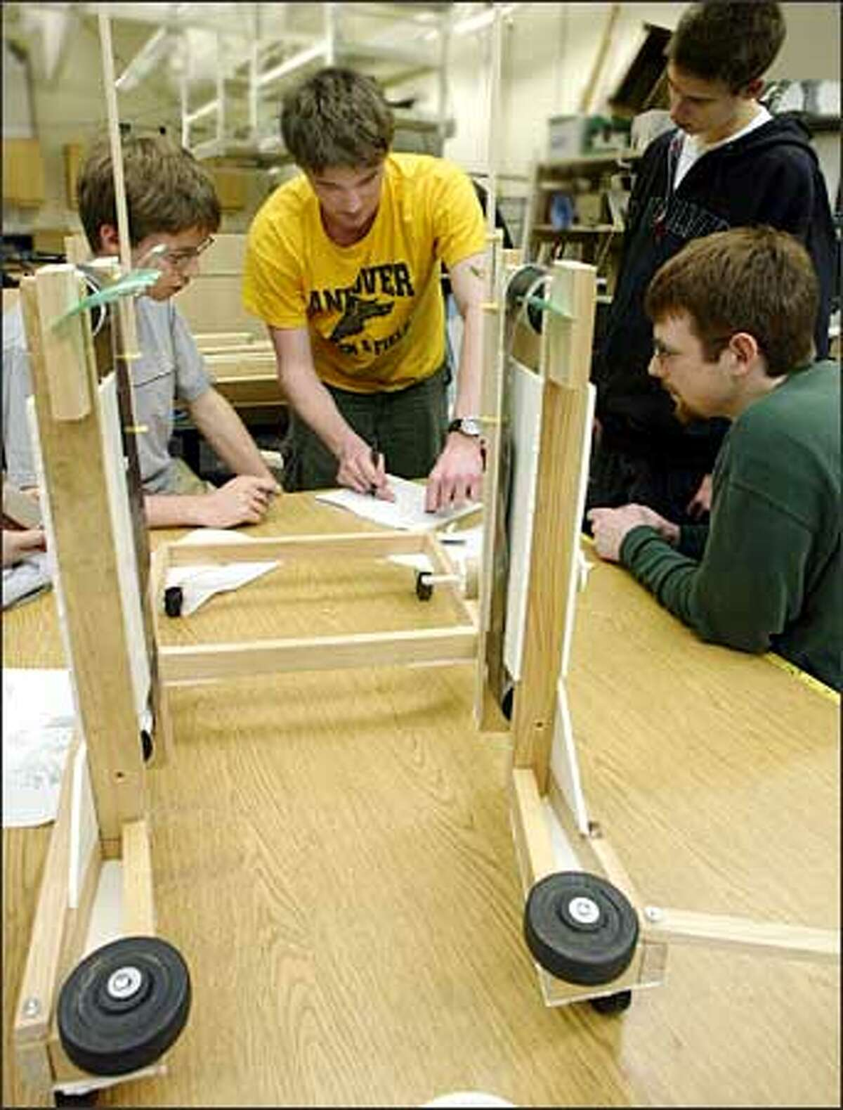 Roosevelt student Nik Krumm, left, works with UW electrical engineering students Ryan Domigan, Tristan Burch and Eric Hungerford.