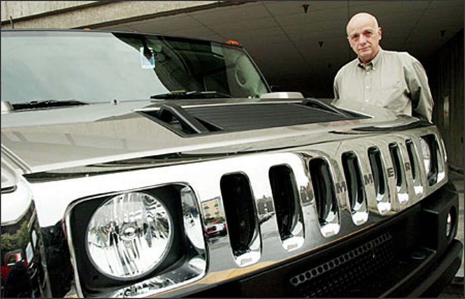 """Real estate broker John Brightbill stands beside his Hummer H2. He is considering the tax write-off -- """"I've been using it partially for business."""" Photo: Gilbert W. Arias/Seattle Post-Intelligencer"""
