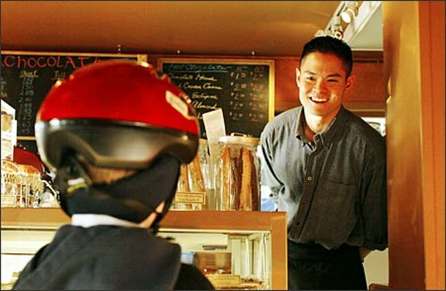 Christian Wong, owner and chief chocolate officer of Sutliff Candy Co., speaks with customer Chase Fowler, 5, of Kent at his newly opened Chocolati Cafe at 7810 E. Green Lake Way N. Photo: Meryl Schenker/Seattle Post-Intelligencer