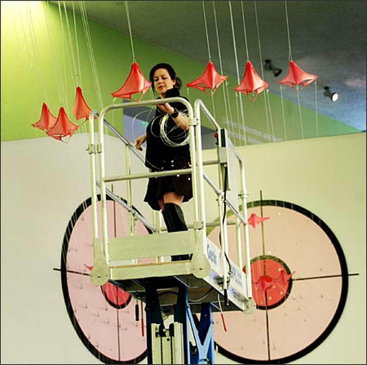 """Working from an aerial lift at the Bellevue Art Museum, E.V. Day hangs her exhibit, """"Intervention of Thongs and G-Strings."""""""