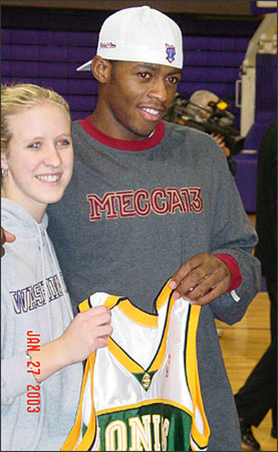 Former UW guard Kayla Burt receives an autographed game jersey from Sonics swingman Desmond Mason. Photo: / Seattle Sonics