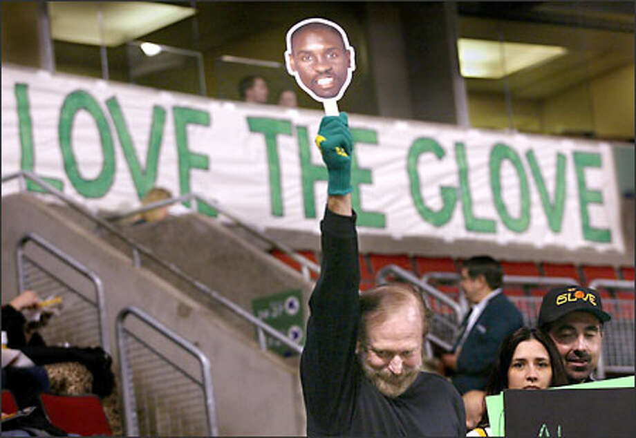 Sonics fan Brian Snyder of Sumner, wearing a glove, holds up a Gary Payton mask and bows his head to protest the trading of the All-Star guard. Photo: Scott Eklund/Seattle Post-Intelligencer
