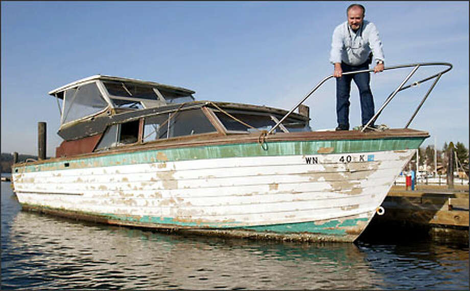 "Port of Poulsbo Harbor Master Ed Erhardt jokingly renamed this cabin cruiser ""My Nemesis"" after trying for months to get rid of the derelict boat. Photo: Mike Urban/Seattle Post-Intelligencer"