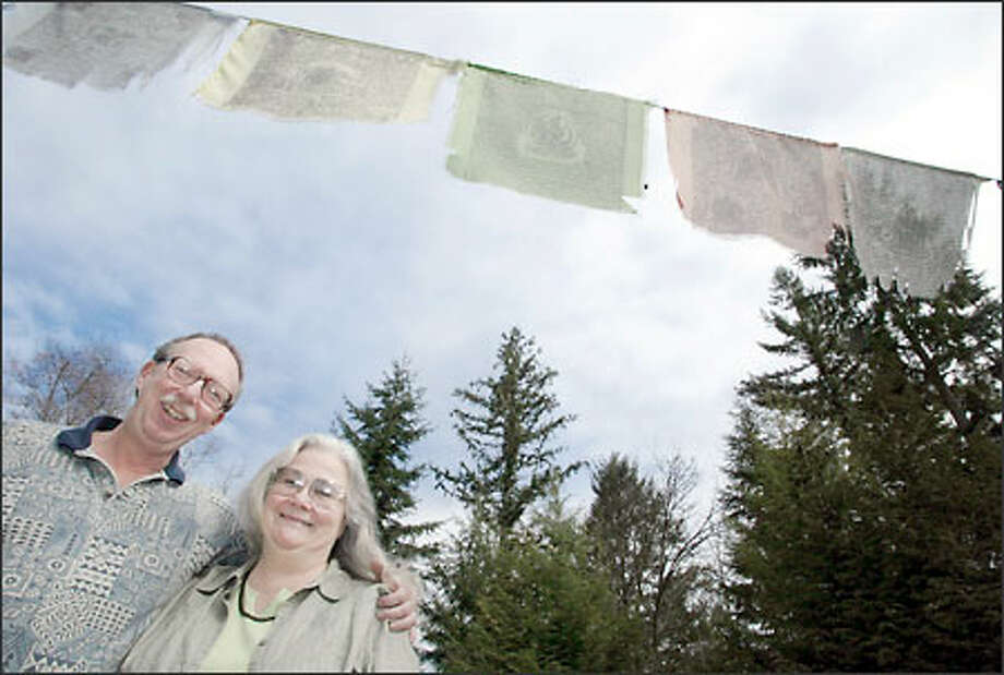 Dr. Sherwin Shinn, a dentist, and his wife, Jerri Shinn, a RN, have been nominated for the Jefferson award for their charitable dental work throughout the world. They live on the Sammamish plateau. Tibetan prayer flags fly above their heads. Photo: Paul Joseph Brown/Seattle Post-Intelligencer