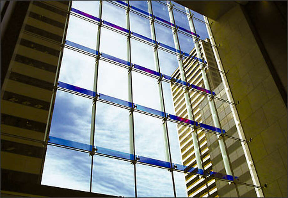 New York-based artist and Pilchuck co-founder Jamie Carpenter designed an iridescent glass piece for the west wall of the Third Avenue lobby (IDX building). Fins of dichroic glass are clipped onto cables and shift color with changes in light and viewpoint. Photo: Meryl Schenker/Seattle Post-Intelligencer