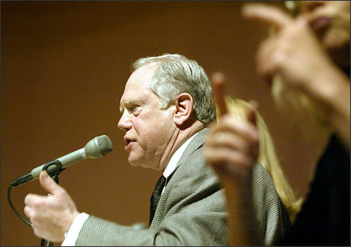 John Sandifer, AFTRA, Seattle Local, is framed by Sign Language Interpretor Janet Gerrard as he testifies as part of a pannel on local news during the FCC Commissioners field hearing on media ownership rules in Seattle at the University of Washington's Hub Auditorium.