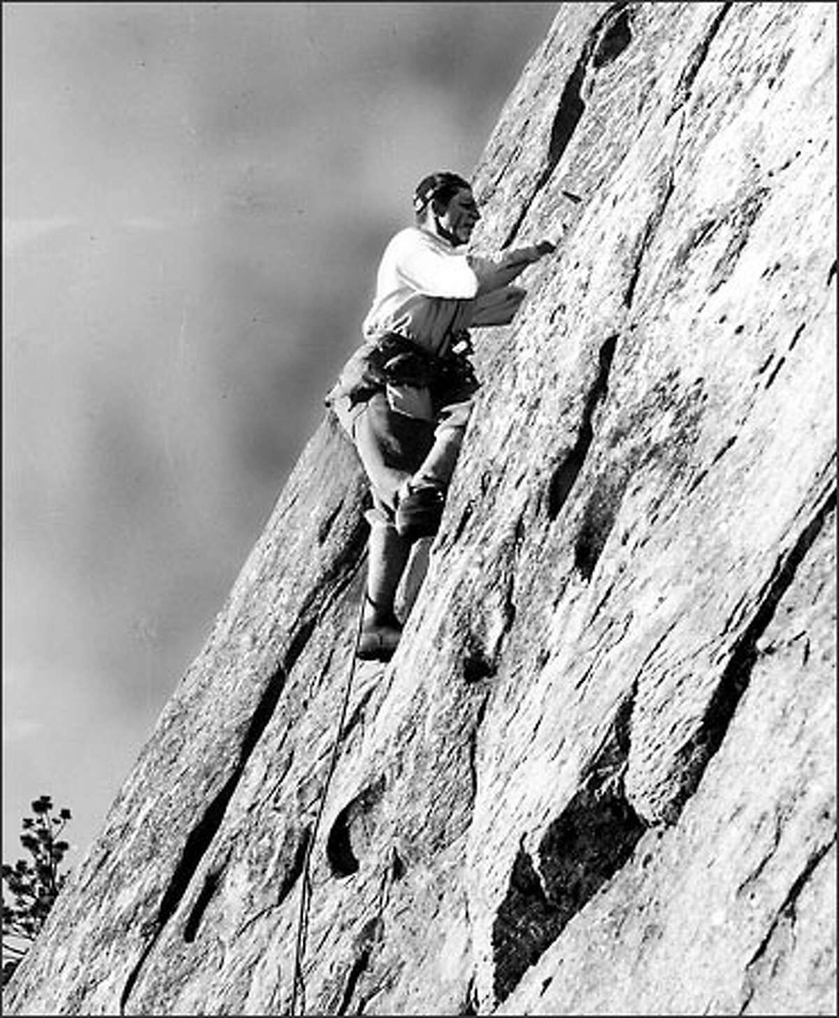 1963-Fred Beckey, mountain climber, on a rock slab.