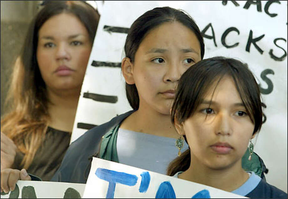 """Cree Okimow, 13, Analisa Zahne,13, and Kira Harvey, hold signs in protest of having the West Seattle High School mascot be an Indian, outside the Seattle school's administration center. Okimow's sign said, """" I am not a mascot."""" Photo: Meryl Schenker/Seattle Post-Intelligencer"""