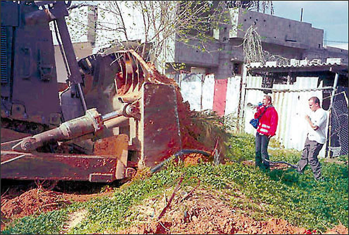 Rachel Corrie uses a bullhorn yesterday as she tries to stop an Israeli bulldozer from razing a Palestinian home. She was killed a short time later.