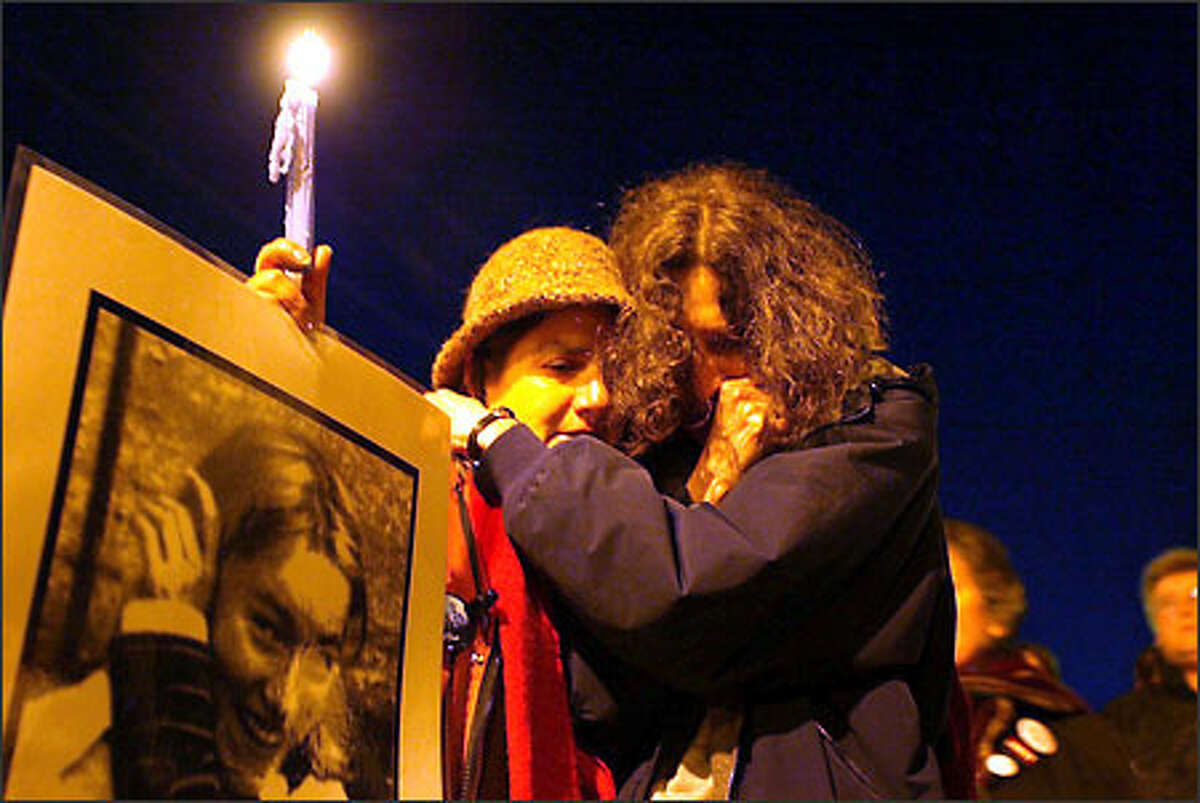 Professors Therese Saliba, left, and Anne Fischel comfort each other at a candlelight memorial for Rachel Corrie yesterday in Olympia.