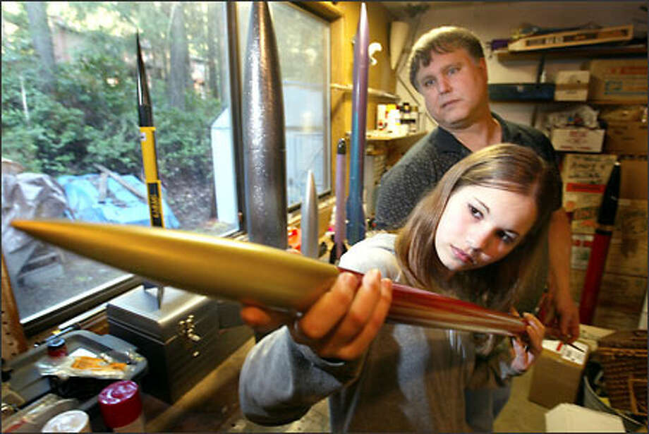 Andrew MacMillen of Poulsbo and his daughter, Katy, check out one of his rockets. MacMillen is the launch director for Washington Aerospace, a club for model-rocket enthusiasts. Photo: Scott Eklund/Seattle Post-Intelligencer