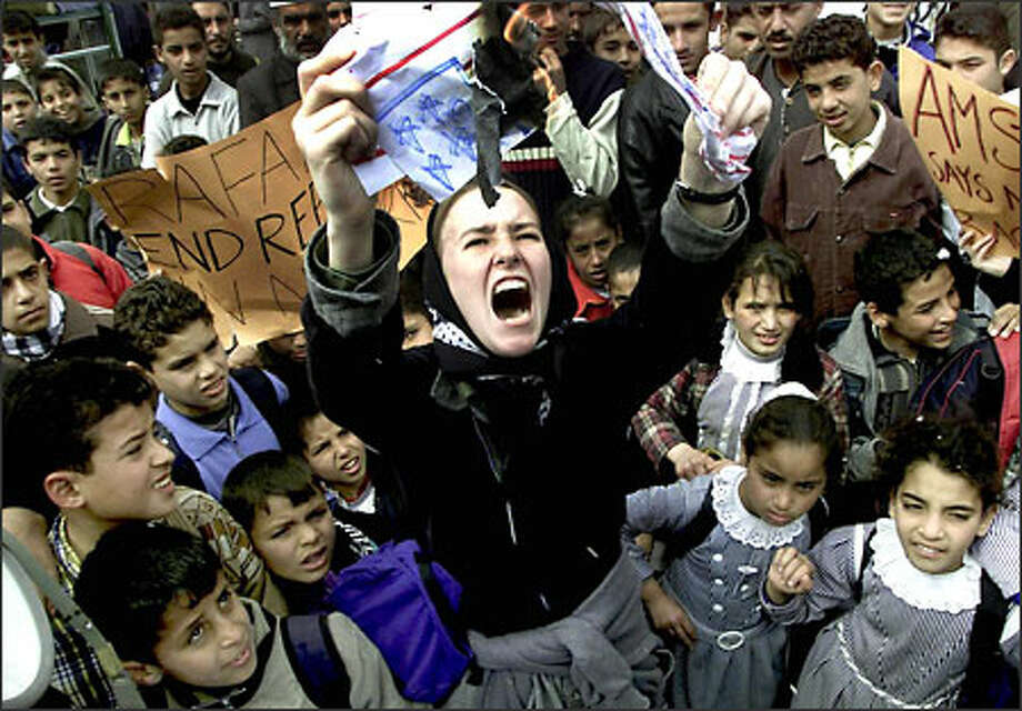 Rachel Corrie burns a mock U.S. flag during a February rally in the Gaza Strip. The activist from Olympia was killed Sunday by an Israeli army bulldozer. Photo: / Associated Press