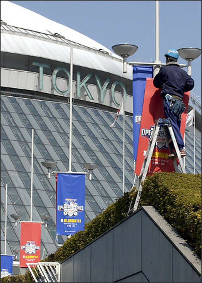 A worker removes banners outside the Tokyo Dome, where the Mariners and Oakland A's were to have played. Photo: / Associated Press