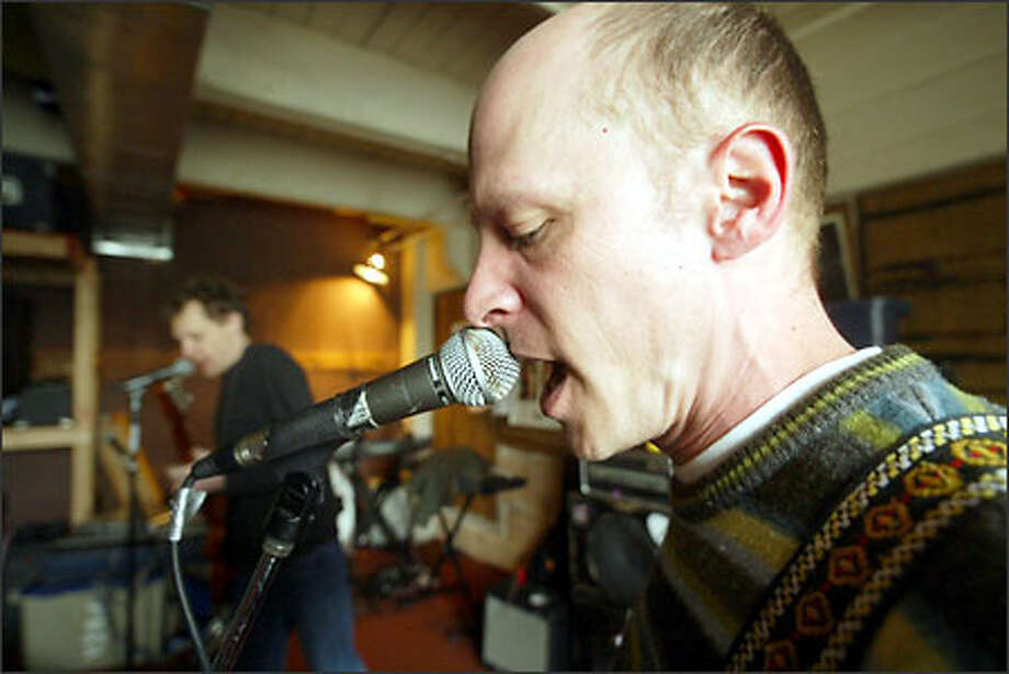 Singer-bassist Chris Ballew and guitarist Dave Dederer (in the rear) rehearse on Capitol Hill. Ballew still plays the Kawai guitar he bought at a pawn shop years ago for $60. Photo: Phil H. Webber/Seattle Post-Intelligencer