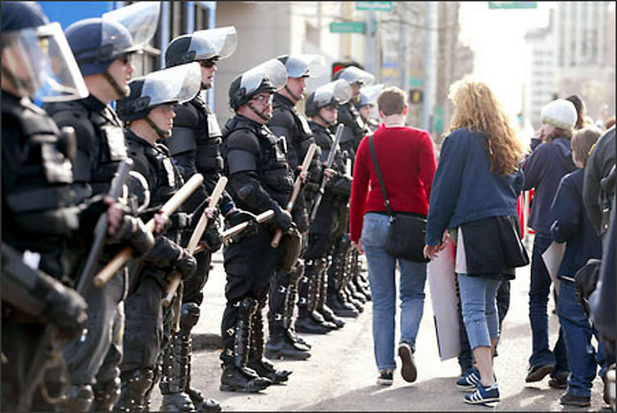 Seattle police in full riot gear flank anti-war protesters as they march toward downtown Seattle Thursday afternoon.