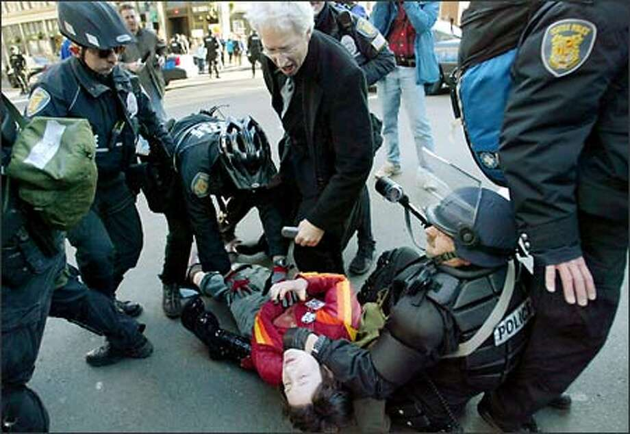A protester is arrested on First Avenue during confrontations with Seattle police as she attempted to march in downtown Seattle during an anti-war rally.  A man who claimed to be her lawyer jumped out to help her and was also arrested. Photo: Meryl Schenker/Seattle Post-Intelligencer