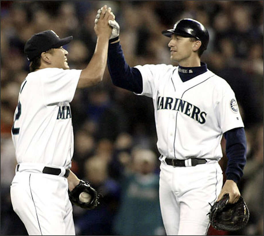 Relief pitcher Kazuhiro Sasaki high-fives first baseman John Olerud after the Mariners defeated the Athletics. Photo: / Associated Press