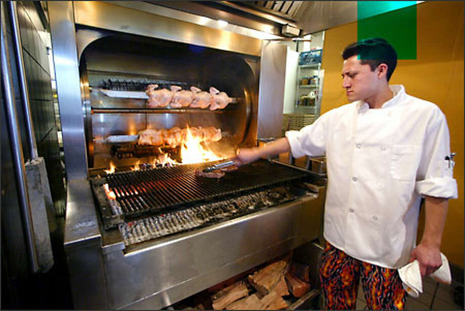 Meat chef Vicente Naal lays a slab of beef on the grill at Matts' Rotisserie & Oyster Lounge in Redmond. Other offerings include chicken, pork and seafood, including six varieties of oysters. Photo: Jim Bryant/Seattle Post-Intelligencer