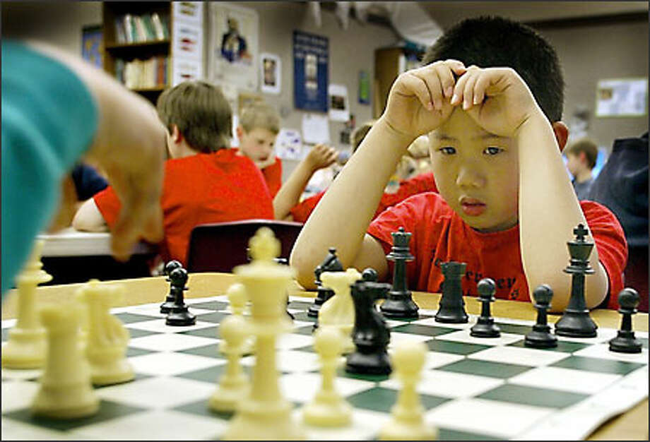 Bobby Luo considers his next move during a chess game with Nat Mayer, right. Both are in The Evergreen School's chess club. Photo: Gilbert W. Arias/Seattle Post-Intelligencer
