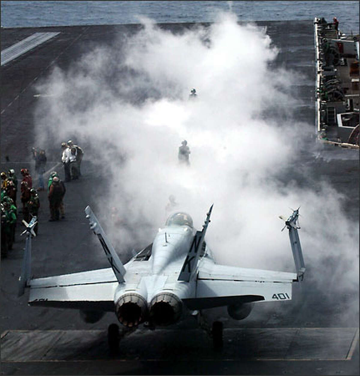Steam rises from a catapult as the flight crew prepares to launch an F/18 Hornet yesterday -- the last of the carrier's combat planes to leave the ship.
