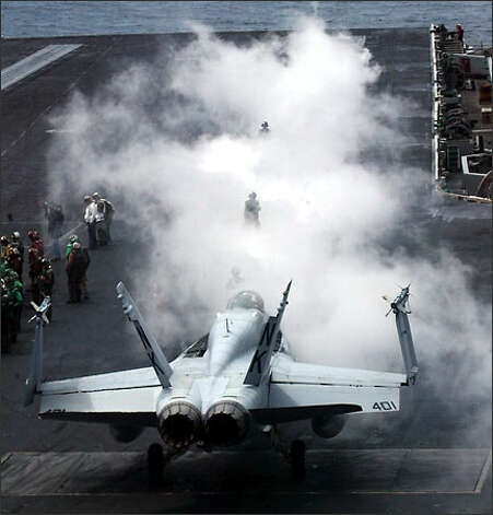 Steam rises from a catapult as the flight crew prepares to launch an F/18 Hornet yesterday -- the last of the carrier's combat planes to leave the ship. Photo: Grant M. Haller/Seattle Post-Intelligencer