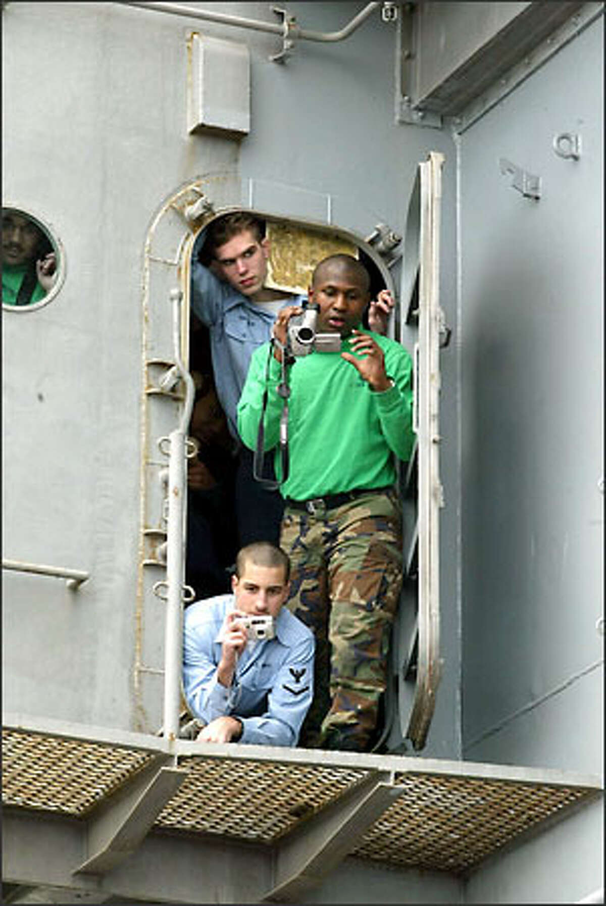 Members of the Abraham Lincoln's crew get a look at the president from a doorway on the carrier's tower.