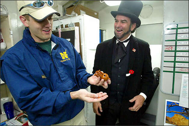 Jim Runge dressed as Abraham Lincoln to greet the ship and his son, Ryan, who shows his dad his pooping reindeer. Like father, like son. Photo: Grant M. Haller/Seattle Post-Intelligencer