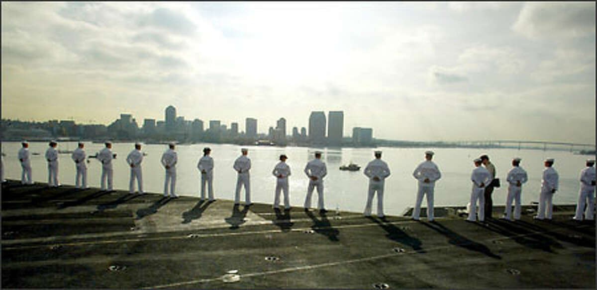 Sailors in their dress whites line the rail of the aircraft carrier as the ship docks in Naval Air Station North Island in San Diego.