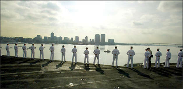 Sailors in their dress whites line the rail of the aircraft carrier as the ship docks in Naval Air Station North Island in San Diego. Photo: Grant M. Haller/Seattle Post-Intelligencer
