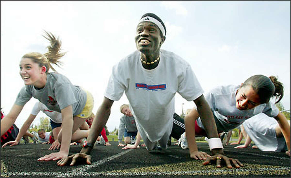 Mathiang stretches with teammates Kiley DeRoche and Tiffany Steele.
