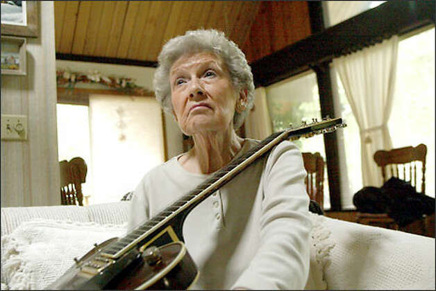 "Fay Draper of North Bend cherishes her husband's guitar, which was always within his reach. She said of her husband, Rusty, who died March 28: ""I know he's singing."" Photo: Phil H. Webber/Seattle Post-Intelligencer"