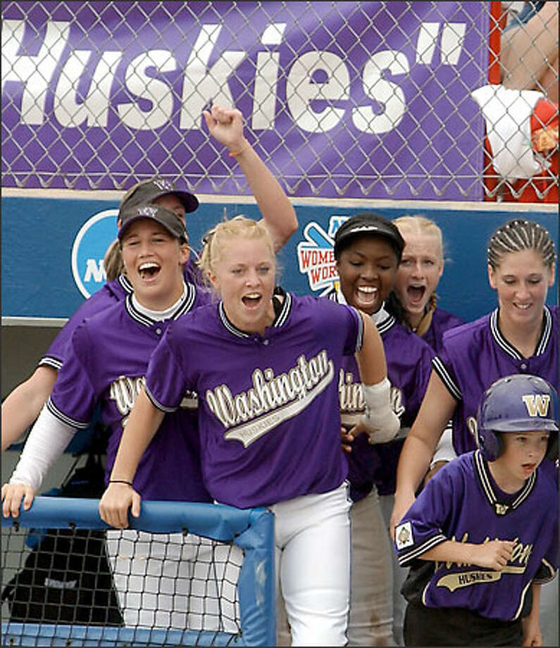 UW players celebrate after Amanda Oleson's two-run double in the seventh broke a tie. Photo: JERRY LAIZURE/AP