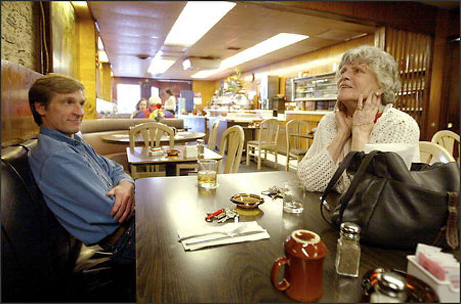 Betty Henderson, owner of Sorry Charlies Restaurant and Piano Bar, reminisces about the glory days of her once thriving business with Drew Curry, owner of Uptown Florists, who is closing his business after 16 years. Photo: Scott Eklund/Seattle Post-Intelligencer
