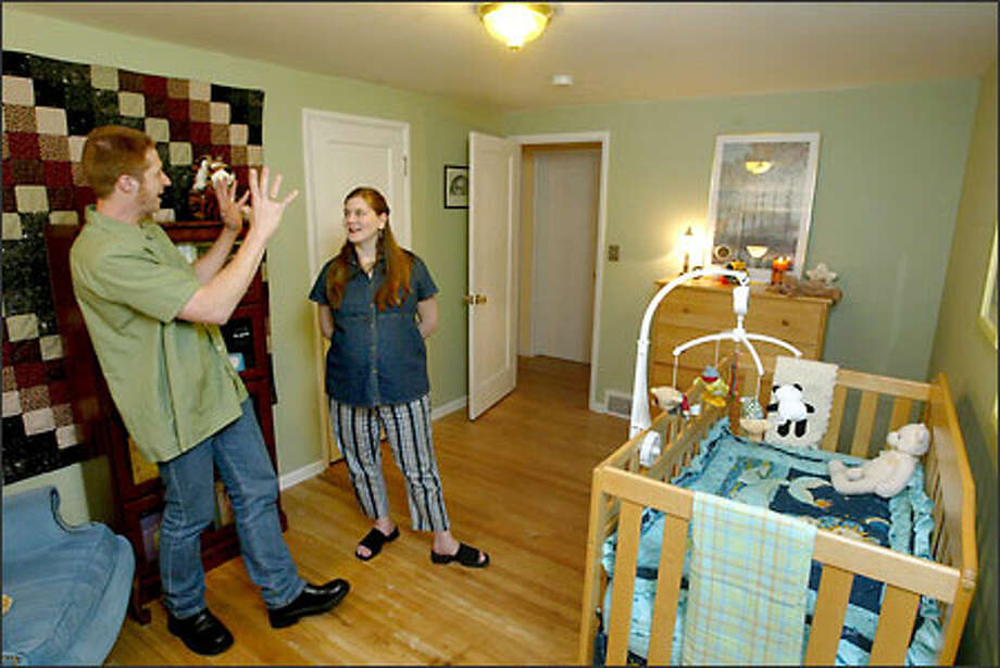 Standing in the new baby room, made over from a guest room, Mark Ford and Candace Ives are happy with the transformation of their home and think it will help them sell the house. Photo: Scott Eklund/Seattle Post-Intelligencer