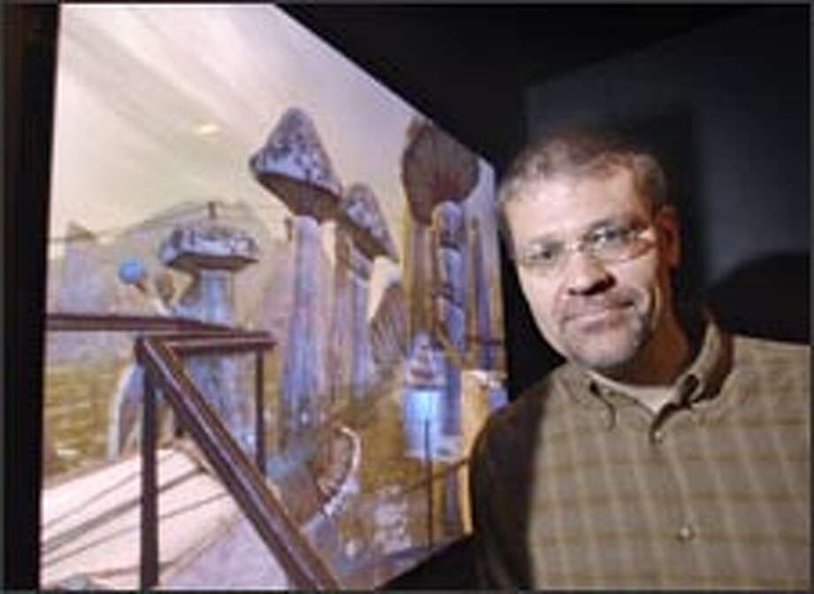 "Rand Miller, who with his brother created ""Myst"" in 1993, poses with an image from his new multiplayer online game, ""Uru: Ages Beyond Myst."" Photo: AP / AP"